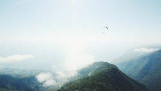 山の上をパラシュートが飛んでいる