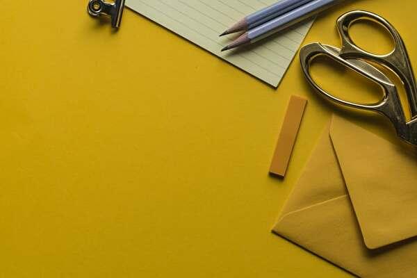 黄色い画用紙に文房具が置いてある